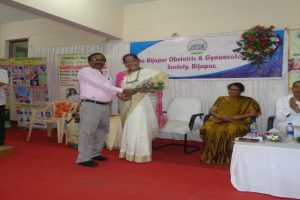 Dr.S.R.Mudnaur-giving-the-flower-bouque-to-Dr.Mrs_.Thobbi-Al-Ameen-Medical-college-Vijayapur.-23-06-2018.jpg